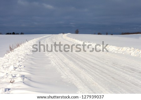 Rural road in winter time, Latvia, Europe.