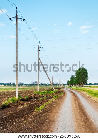 Rural road passing along the electric poles - stock photo