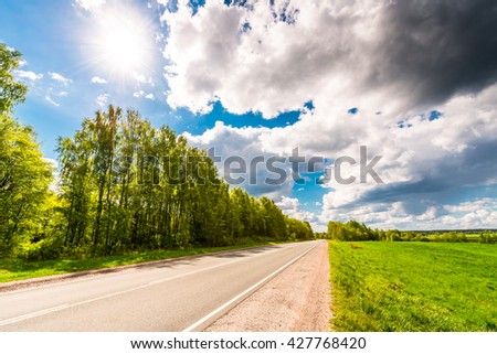 Rural road passing through fields and woods illuminated by the sun. View from the side of the road - stock photo