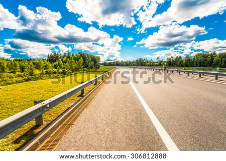 Rural road passing through forest. View from the road - stock photo