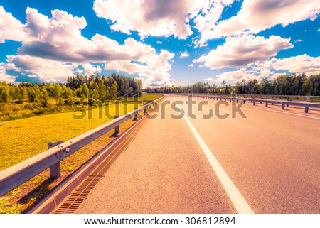 Rural road passing through forest. View from the road, image in the orange-blue toning - stock photo