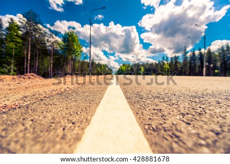 Rural road passing through the forest. View from the level of the dividing line, focus on the asphalt, image vignetting and the yellow-blue toning - stock photo