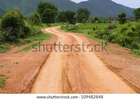 Rural road through green fields with mountain and cloudy sky, Thailand. - stock photo