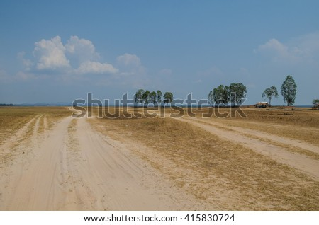 rural road under dramatic cloudy sky - stock photo