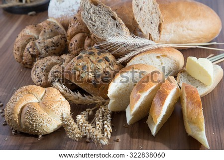 Rural rolls and bread with butter and spikes of wheat - stock photo