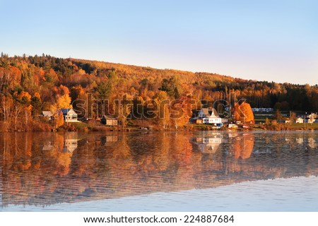 Rural scene during Fall or Autumn along the Saint John River in New Brunswick, with reflection of colorful trees along the water  - stock photo