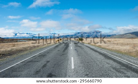 Rural Scene of Asphalt Road with Meadow and Mountain Range, South Island, New Zealand - stock photo
