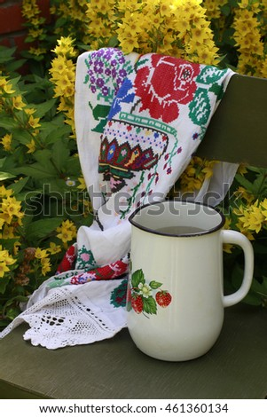Rural scene: vintage original wooden Vienna chair, handmade embroidered linen towel with lace and old white enamel jug, high angle view, vertical picture