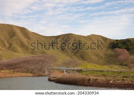 rural scene with bridge and river running to tidal lagoon near Gisborne, New Zealand  - stock photo