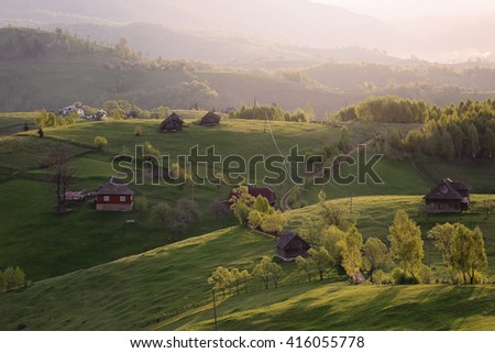 Rural scenery with early morning sunlight over the hills and valleys in Sirnea-Bran area, Sirnea village, between Brasov and Arges county, Romania - stock photo