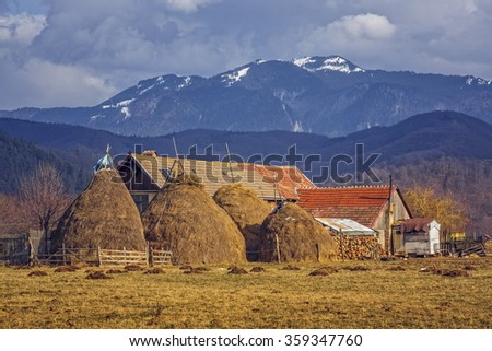 Rural scenery with traditional Romanian rustic farm with haystacks and grassland in the backyard, near Postavaru massif, Brasov county, Romania. - stock photo
