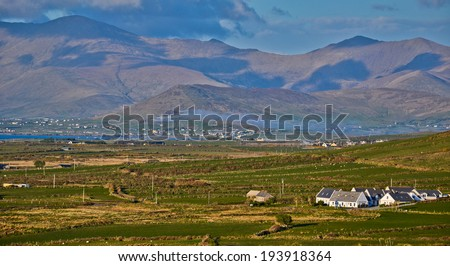 Rural Spring Irish Landscape: Typical mountain and houses landscape from the west coast of Ireland in County on dingle peninsula or ring of kerry.Popular destination for tourism and holiday homes - stock photo