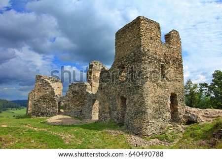 Rural stone ruins of gothic castle Brnicko, Czech Republic, Europe. Green grass, medieval castle architectue and sky with clouds. Old ruin with grass, sky and clouds.Summer outdoor trip to a ruin.
