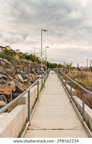 Rural suburban paved pedestrian walkway with metal handrails under overcast sky, perspective view. Rocky hillside with lights along the path. Swirling clouds overhead. Copy space.   - stock photo
