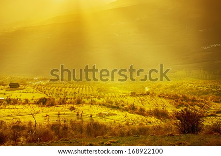 Rural sunset landscape with green hills, dramatic sky, mountains and sun rays - stock photo