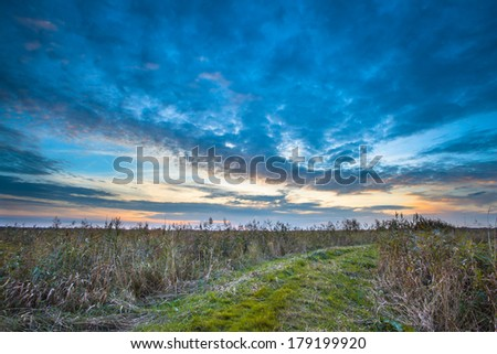 Rural Trail through Grassy Field on Lakeside during Sunset leading to Heaven - stock photo
