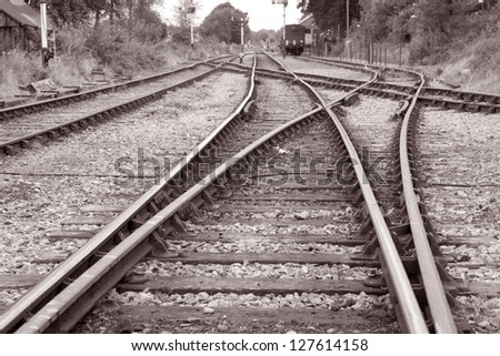 Rural Train Tracks with Train in Background in Black and White Sepia Tone - stock photo