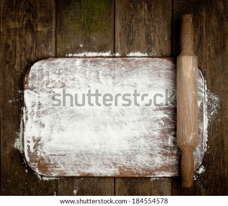 Rural vintage wood kitchen table with blank cook book and cooking tools.  Background with free recipe text space. - stock photo