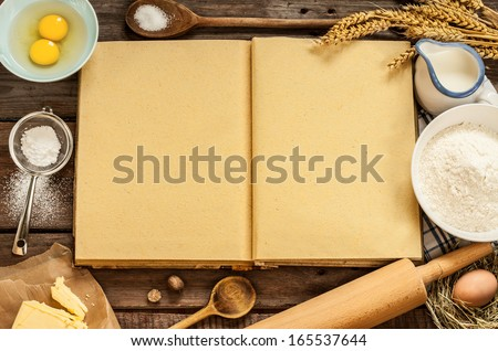 Rural vintage wood kitchen table with blank cook book, baking cake ingredients (eggs, flour, milk, butter, sugar) and cooking utensils around. Country background with free recipe text space. - stock photo