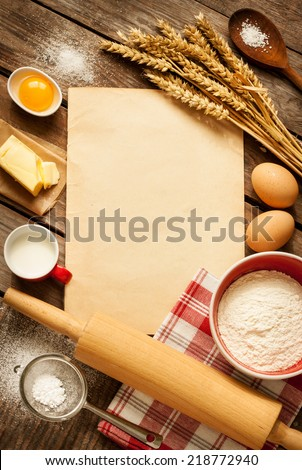 Rural vintage wooden kitchen table with old blank sheet of paper, baking cake ingredients (eggs, flour, milk, butter, sugar) and cooking utensils around. Background with free recipe text space. - stock photo