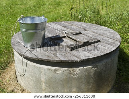 Rural well with metal bucket. - stock photo