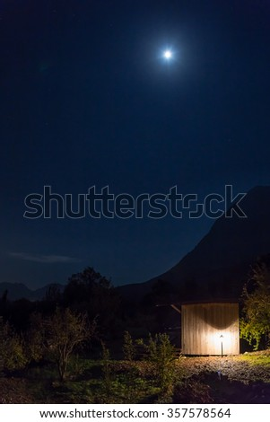 Rural Wooden Bungalow at Night illuminated in Mountains Silhouette of rocky Ridge and Moon shining on sky - stock photo