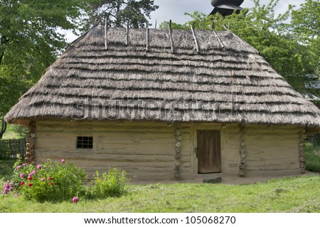 Rural wooden clay covered cottage with a straw roof. Ukraine.