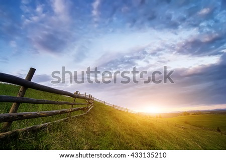 rural wooden fence. natural summer landscape with blue cloudy sky on sunset. natural summer background - stock photo