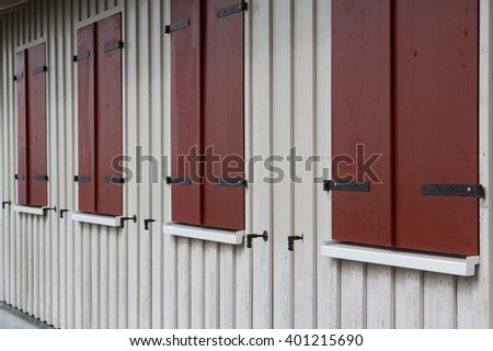 rural wooden house exterior with closed window shutters