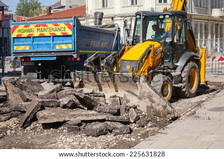 Ruse, Bulgaria - September 29, 2014: Road works. Highway maintenance, yellow tractor removes old asphalt pavement and loads it in a blue industrial truck - stock photo