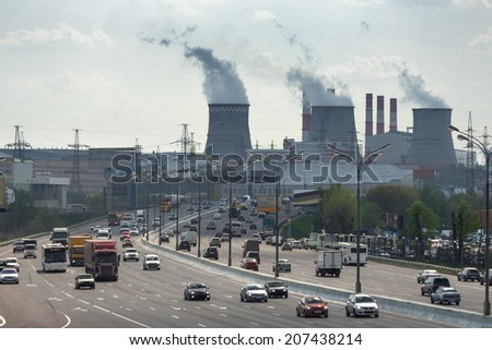 Rush hour traffic at the wide road opposite the fuming tubes of the thermal power station - stock photo