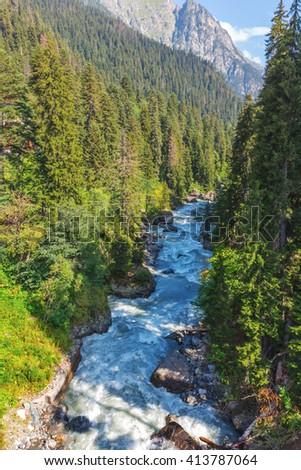 rushing blue river in a mountain canyon - stock photo