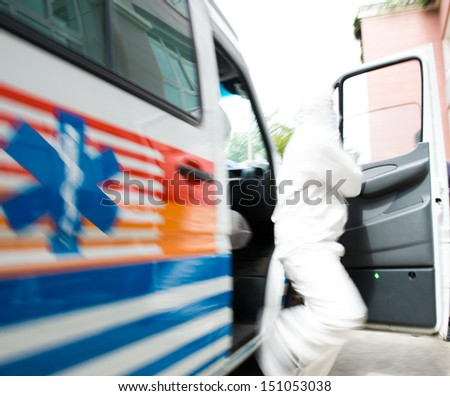 Rushing blurry paramedic man out  of ambulance car. - stock photo