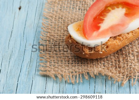 Rusk sandwich with egg and tomato on old wooden table - stock photo