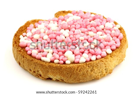 rusk with white and pink anise seed sprinkles served in Holland when a baby girl is born on a white background - stock photo