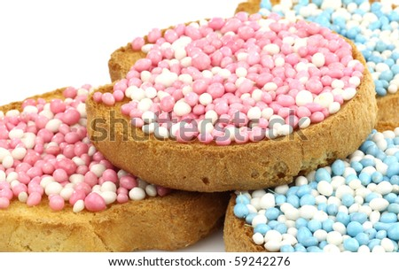 rusks with white and blue and white and pink anise seed sprinkles served in Holland when a baby boy or girl is born on a white background - stock photo