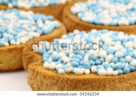 rusks with white and blue anise seed sprinkles served in Holland when a baby boy is born on a white background - stock photo