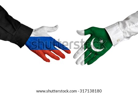 Russia and Pakistan leaders shaking hands on a deal agreement - stock photo