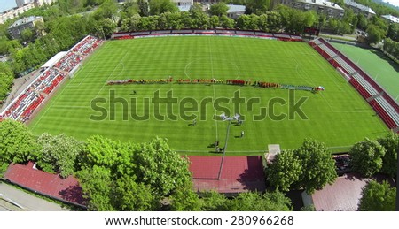 RUSSIA, BOGORODSKOE - MAY 14, 2014: Teams play soccer on field of Spartakovec stadium named by N.P. Starostin during international competition. Aerial view - stock photo