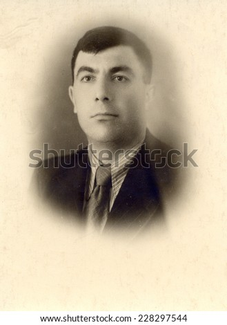 Russia, - CIRCA 1948: An antique studio portrait of young man in a business suit.