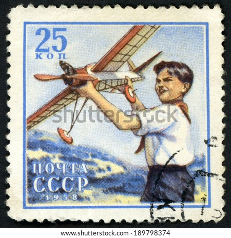 RUSSIA - CIRCA 1958: post stamp printed in USSR (CCCP, soviet union) shows smiling boy holding model plane from Pioneers design series, Scott 2069 A1089 25k blue white red, circa 1958