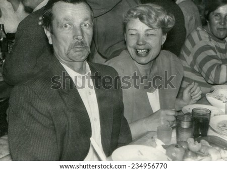 RUSSIA - CIRCA 1950s: An antique photo shows portrait of a Mature man and woman at the banquet table. - stock photo