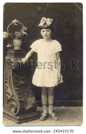 RUSSIA - CIRCA 1927 Vintage photo shows portrait an unidentified girl standing in white dress - stock photo