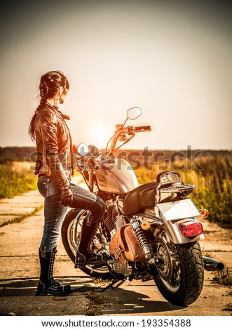 RUSSIA-JULY 7, 2013: Biker girl and bike Harley Sportster. Harley Davidson sustains a large brand community which keeps active through clubs, events, and a museum. Filter applied in post-production. - stock photo