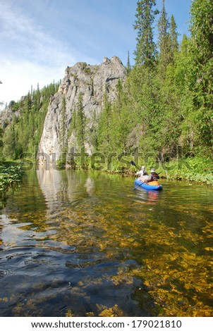 Russia, Komi Republic, summer, taiga. Canoe sailing against the background of the cliff. - stock photo