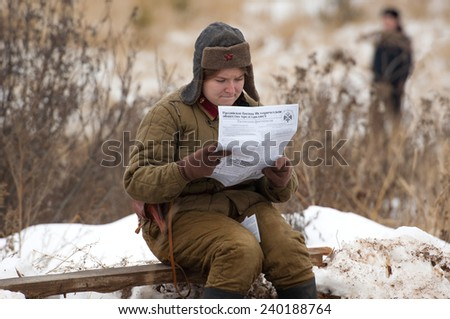 RUSSIA, LIZLOVO - DECEMBER 14: Unidentified woman reading a newspaper on reenactment of the counterattack under the Moscow in 1941 in World War II, in Moscow region, Lizlovo village, Russia, 2014 - stock photo