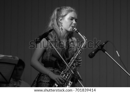Russia, Moscow, 20 August 2017 - Jazz Festival in Hermitage Garden, the girl playing the saxophone - Black and white photo