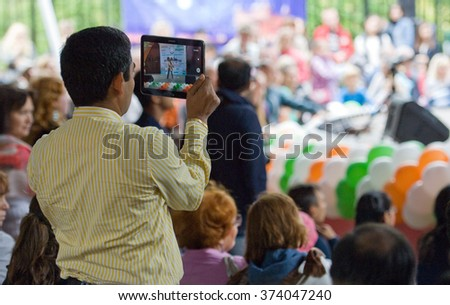 RUSSIA, MOSCOW - AUGUST 16, 2015: Unidentified indian man filming a dance of Center of India folk art on Independence Day of India in Sokolniki park, Moscow, Russia - stock photo