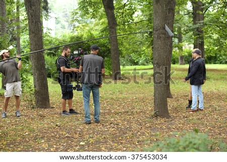 RUSSIA, MOSCOW - 30 JUL, 2015: Five men are standing in the Sokolniki park and shooting movie (Maximum shock). - stock photo