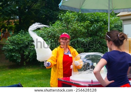 Russia, Moscow, July 8, 2014 - Woman selling cotton candy or candyfloss at the Park of Culture and Rest Gorky.  - stock photo
